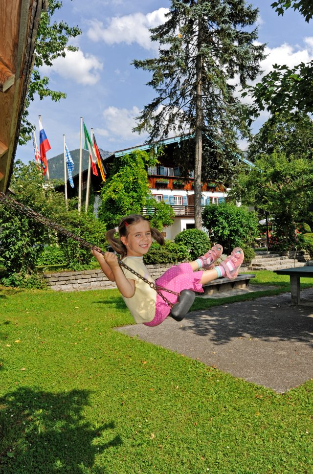 Kinder schaukeln auf dem Spielplatz im Stoll's Hotel Alpina in Schönau am Königssee / Berchtesgaden
